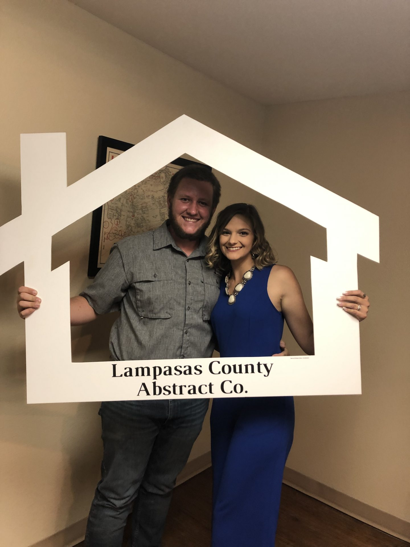 A man and woman holding a Lampasas County Abstract Co. sign.
