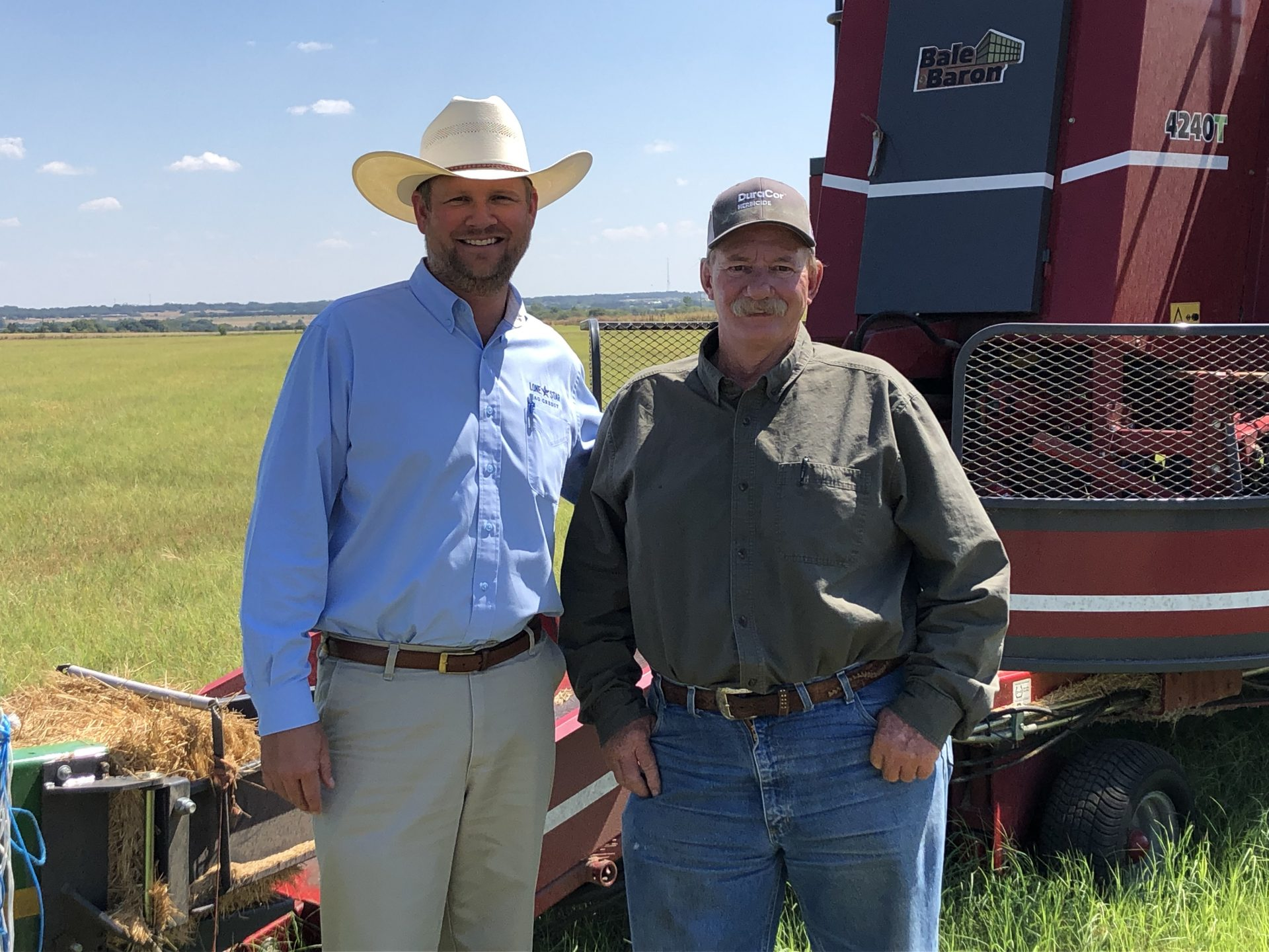 Lone Star Ag Credit Georgetown office Vice President Lending Nathan Winstead with customer in front of hay baler.