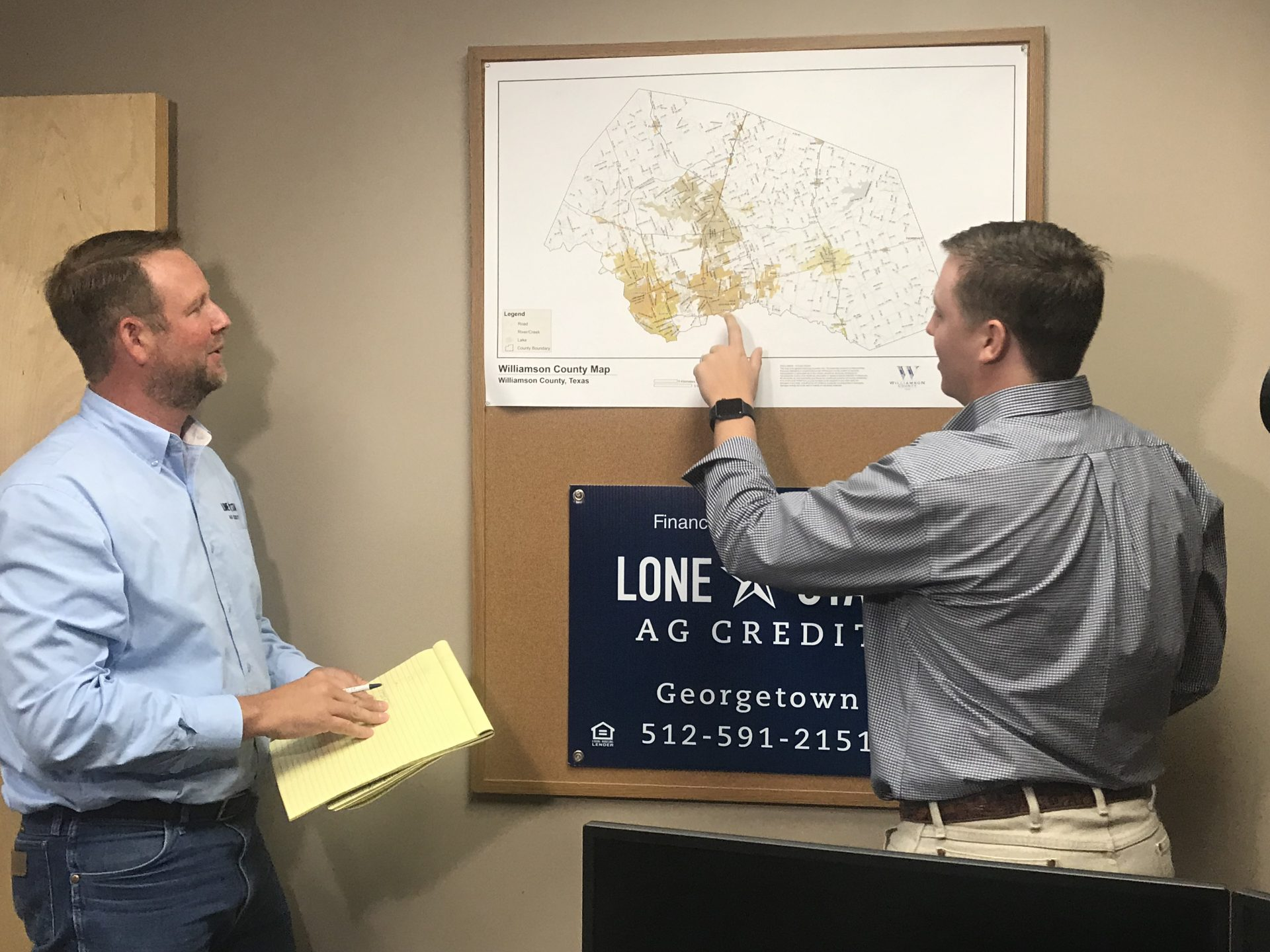 Lone Star Ag Credit loan officers, Nathan Winstead and Tyler Rosser looking at a map.