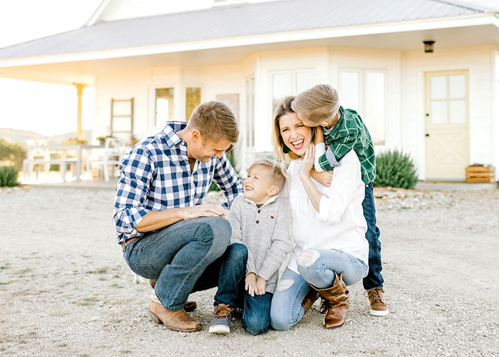 Parents and two kids in front of a white colored home.