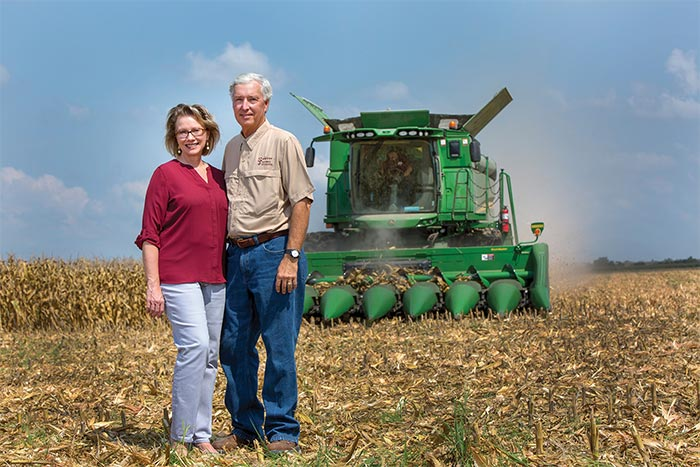 John and Natasha Sawyer in field with combine in the background.