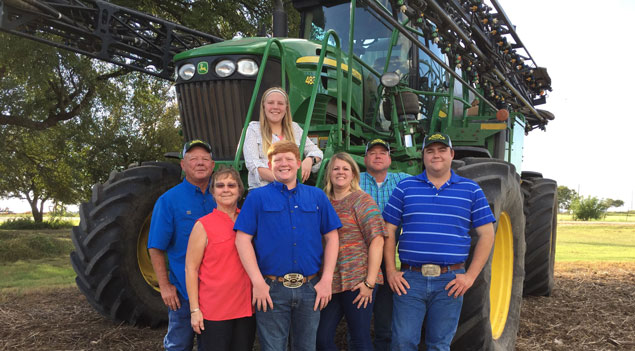 Family standing in front of John Deere tractor.